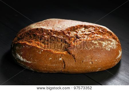 Whole black bread on wooden table close-up