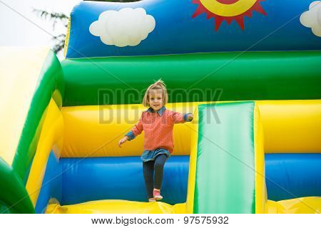 little girl playing on a trampoline.