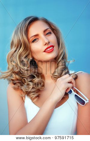 Portrait of a beautiful blond girl with shite sunglasses