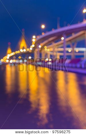 Abstract blurred bokeh light of high way intersection and water reflection during twilight