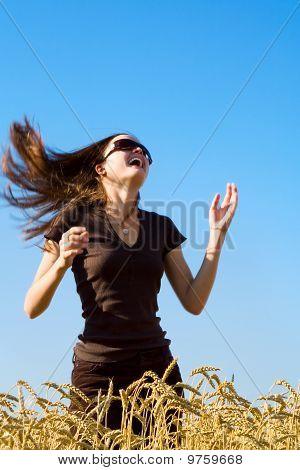 Woman Running Across A Field Of Wheat
