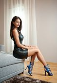 Beautiful sexy brunette young woman wearing black leather short dress sitting on bed poster
