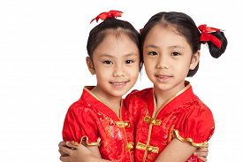 stock photo of identical twin girls  - Asian twins girls in chinese cheongsam dress isolated on white background - JPG
