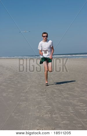 JACKSONVILLE BEACH, FLORIDA - FEBRUARY 14: Runner Frankie Pfeil, age 16 of Lockport, NY,  finishes in third place in the 5 mile Winter Beach Run on February 14, 2010 in Jacksonville Beach, Florida.