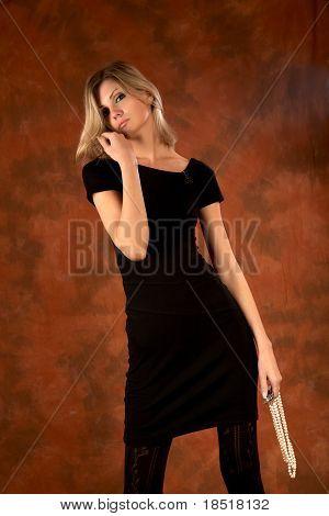 A menina pensativa com miçangas pérolas na mão