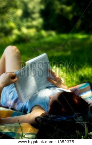 Young Woman Laying Reading Book