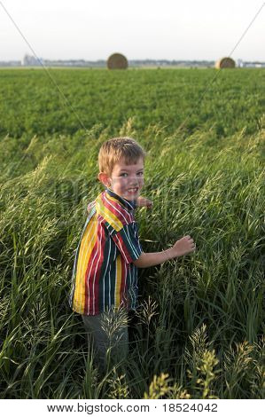 happy farmboy walking through a field in south dakota