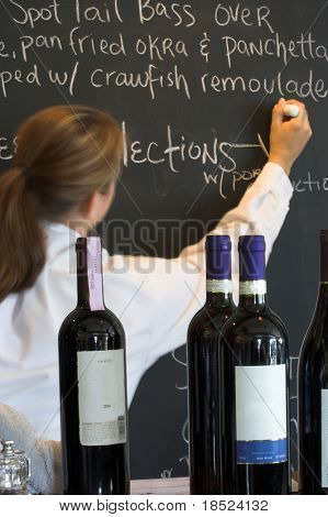 waitress writing menu on menu board, wine bottles in foreground, labels cloned out, focus on foreground