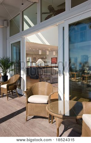 sun porch with large glass doors looking into luxury home