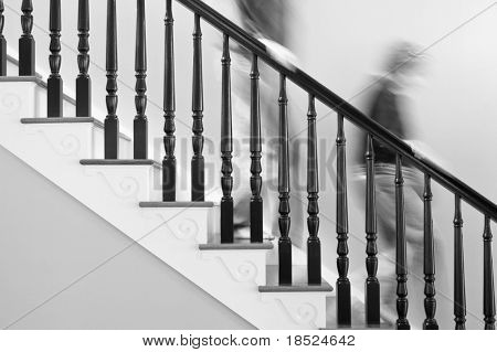 Man and woman rushing down stairs, people blurred by motion, stairs clear, black and white
