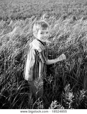 joyful little boy walking through farm field