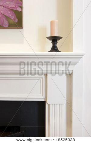 detail of fireplace mantle with candle sitting on it.