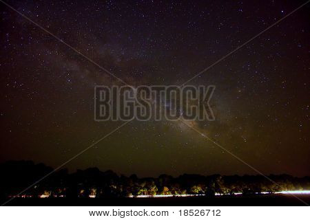 milky way over road with headlight trails