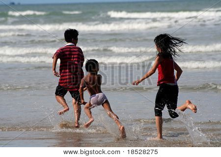 Three children running and playing on the beach