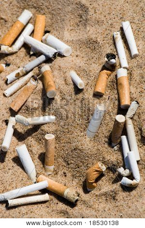 Cigarette butt in sand. Litter on the beach