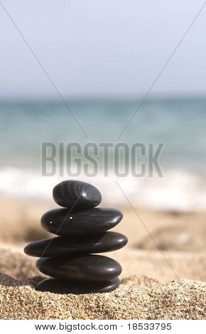 Five Black Stones Pyramid On The Sandy Beach