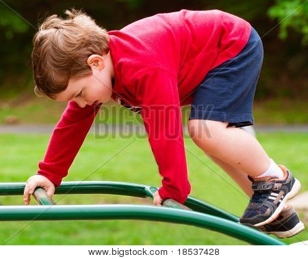 Young boy climbing on playground during spring.