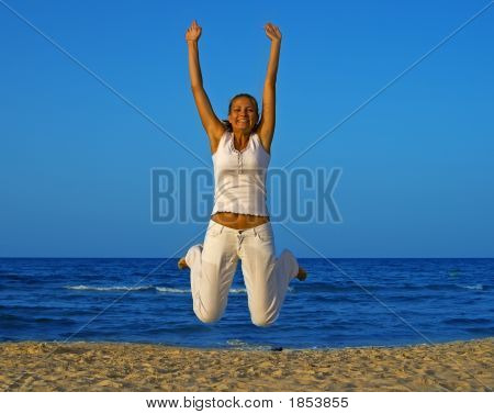 Smiling Girl Jump At The Beach