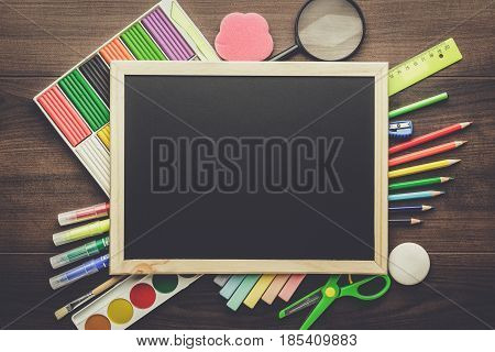 poster of back to school concept. school supplies on the table. clean school blackboard with copy space. preschool and school essentials on the table.