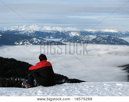 A skier takes a break to contemplate the view from the top of a mountain.
