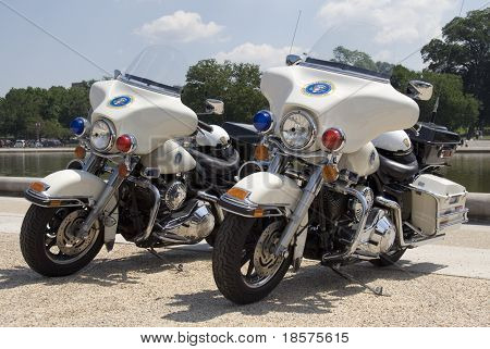 Two Secret Service motorcycles stand near the Reflecting Pool on The Mall in Washington, DC.
