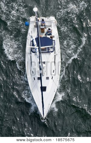 A luxury yacht shot from above as it motors out to sea.