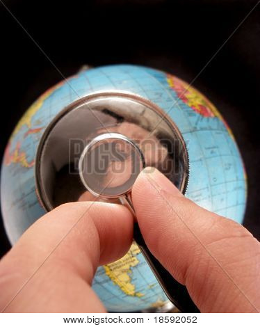 Hand holding stethoscope on the globe