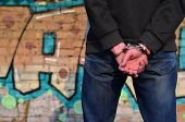 Rear View Of The Arrested And Handcuffed Offender Against The Graffiti Background poster