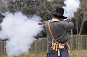 man in colonial clothing firing musket