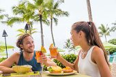 Couple eating at hotel restaurant on Hawaii travel vacation beach drinking hawaiian drink mai tai. H poster