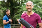 Smiling mature man holding yoga mat and looking at camera. Portrait of a happy mixed race man with y poster