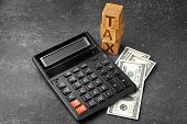 Wooden blocks with word TAX, calculator and banknotes on gray background poster