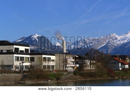 Concrete Chimney At The Background Of Mountains.