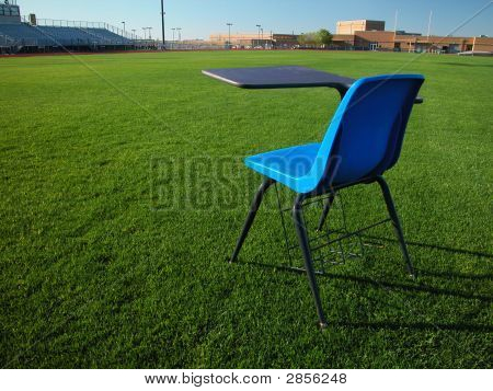 Student Desk On Football Field With School