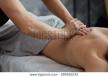 poster of Young Handsome Man Enjoying A Back Massage. Professional Massage Therapist Is Treating A Male Patien