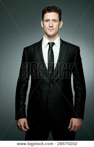 Jovem empresário bonito de terno preto.