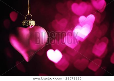 Heart shaped ornament hanging on defocused bokeh background