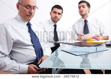 Three businessman, one mature texting using his mobile phone and two young ones sitting at table during meeting
