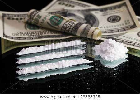Cocaine drugs heap still life on a mirror with rolled 100 dollar bank note, close up view