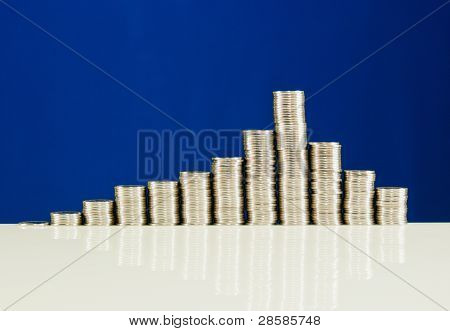 Coins Stacked In Bars Against Blue Background