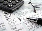 picture of income tax  - multiple tax forms with pen calculator and glasses