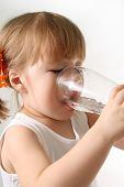 picture of drinking water  - The small girl is drinking water from glass - JPG