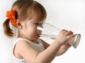 stock photo of drinking water  - The small girl is drinking water from glass - JPG