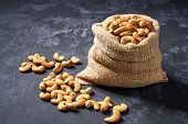 Cashew Nuts  In Burlap Sack On Black Table. Heap Or Stack Of Cashew Nuts . poster