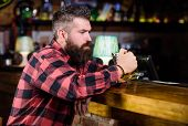 Man With Beard Spend Leisure In Dark Bar. Hipster Relaxing At Bar With Beer. Brutal Hipster Bearded  poster