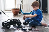 Auto Modeling: Little Boy Repairing A Model Radio-controlled Car At Home. poster