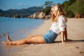 Beautiful Girl In Sea Style Sitting On Sand. Travel And Vacation. Freedom Concept. Sensual Blonde Be poster