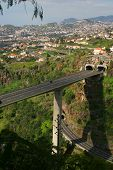 stock photo of skyway bridge  - elevated roadway cut through the mountain side in funchal - JPG