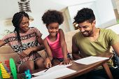 Mom And Dad Drawing With Their Daughter. African American Family Spending Time Together At Home. poster