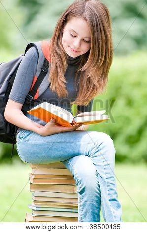 Young Student Girl Sitting On Pile Of Books